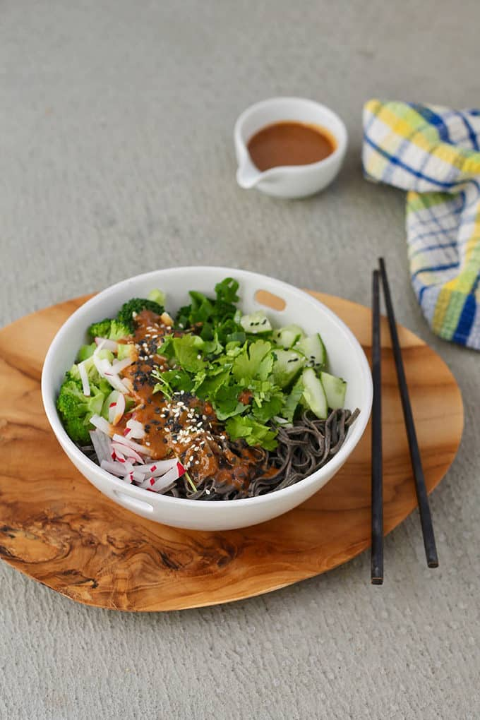 black bean noodles in a white bowl topped with broccoli, cucumber, cilantro, radishes, and peanut sauce