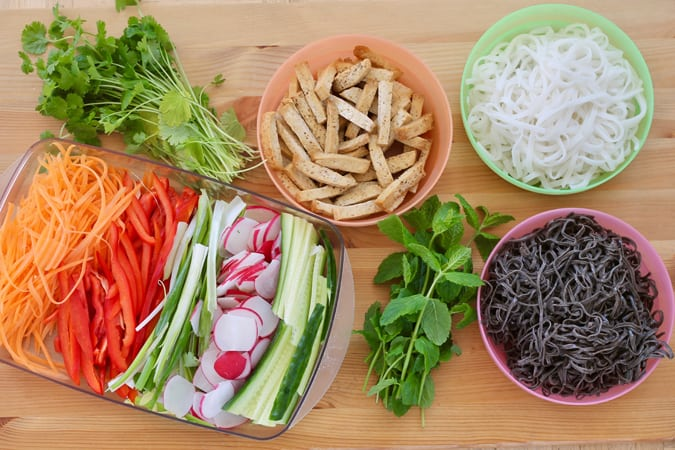 shredded carrot, red pepper, radishes, cucumber, baked tofu, herbs, and noodles on a wooden background