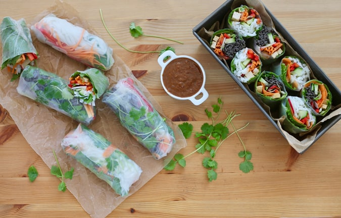 overhead shot of salad rolls in a tin with a pot of dip and some herbs on a wooden background