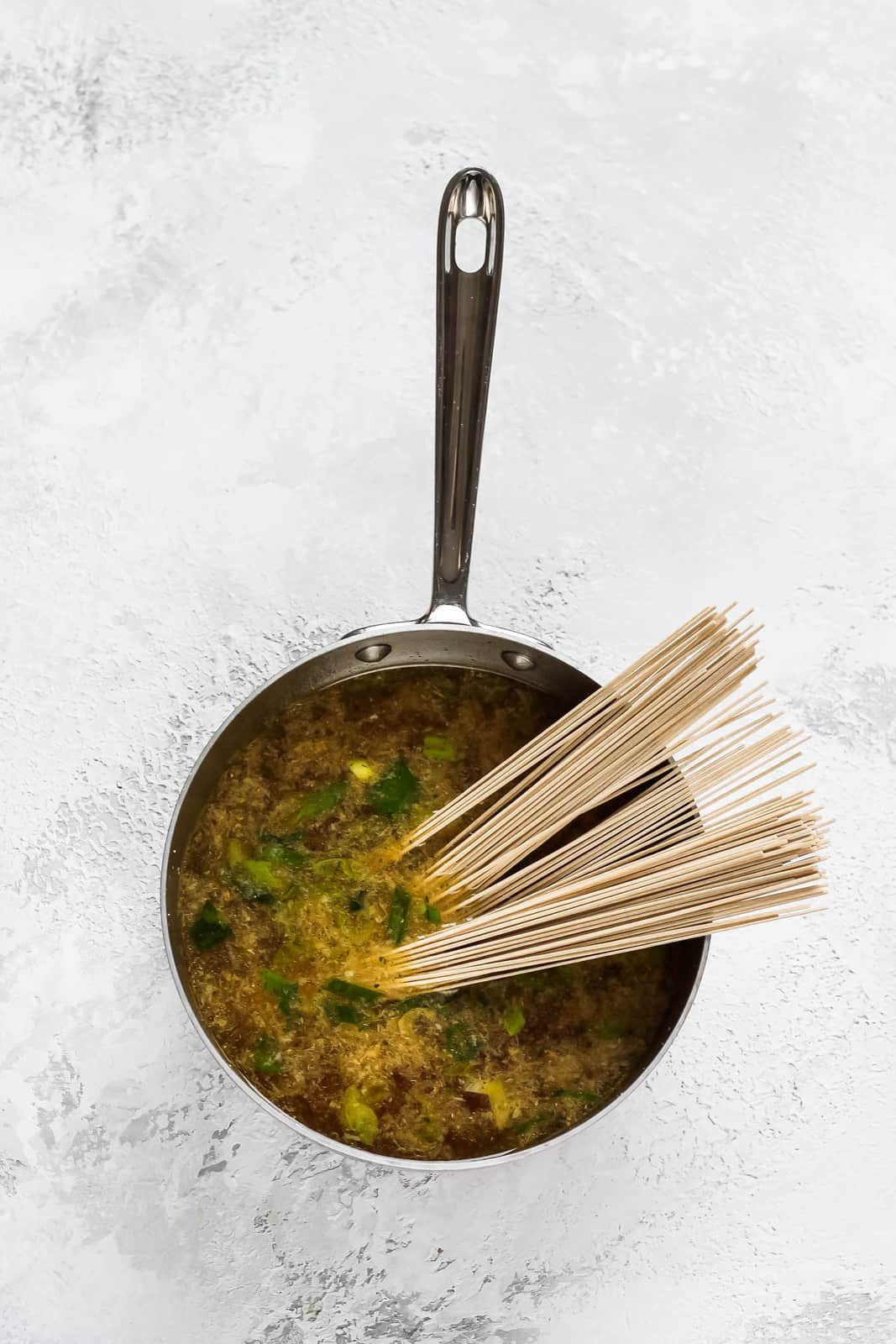 overhead photo of soba noodles in a pot with ramen broth