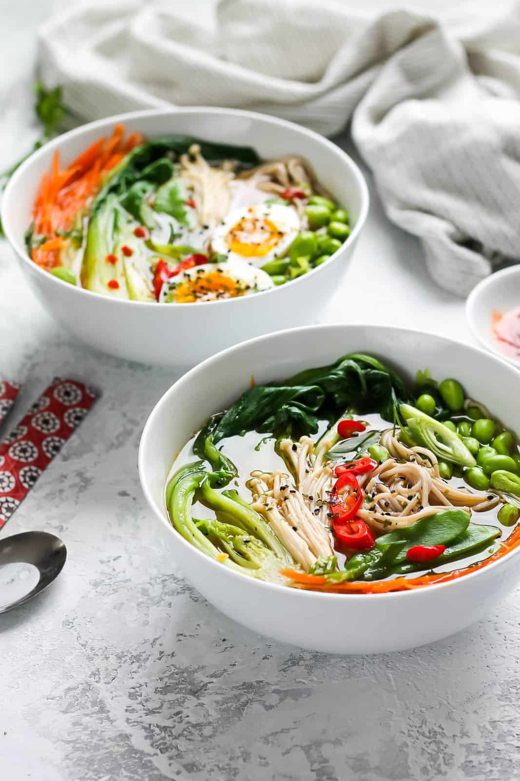 two white bowls with vegetable ramen noodles on a white background