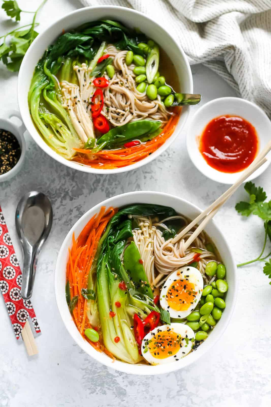 overhead photo of vegetable ramen noodle bowls on a white background