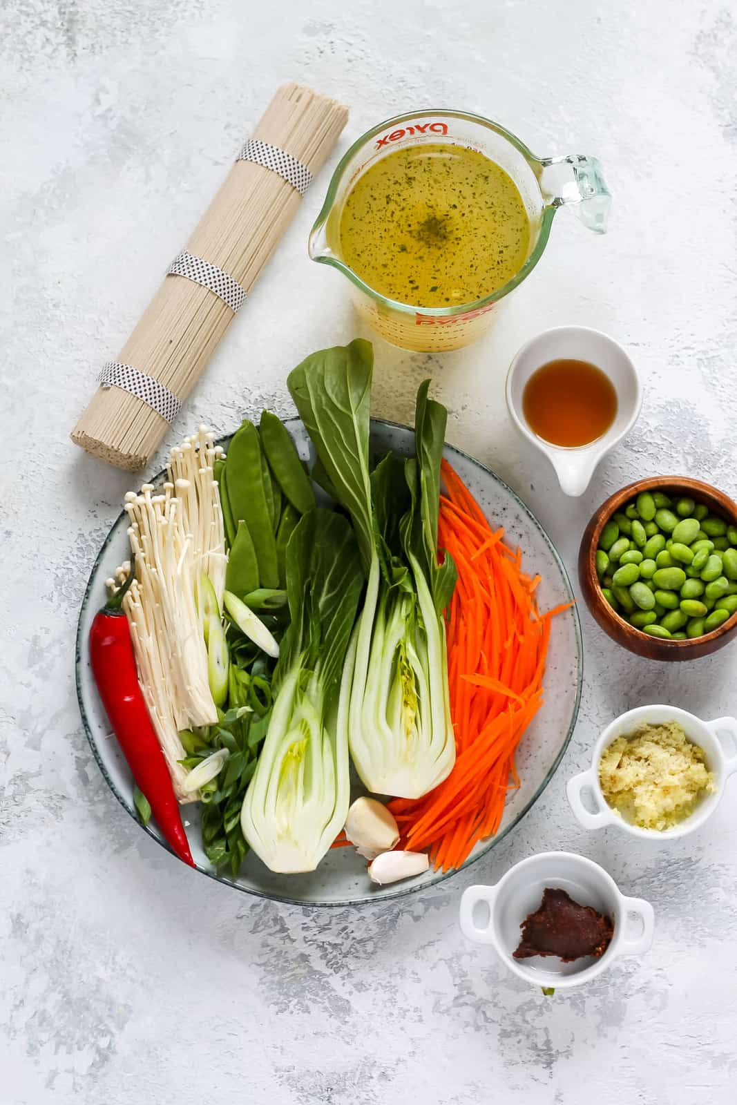 a plate of sliced vegetables, a bunch of ramen noodles, miso, vegetable broth, and edamame on a white background