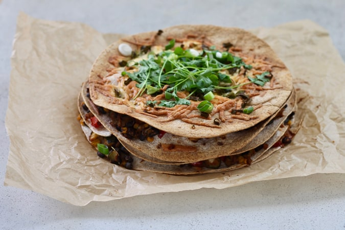 Black Bean Burrito Stack on a piece of brown parchment paper with fresh cilantro sprinkled over top