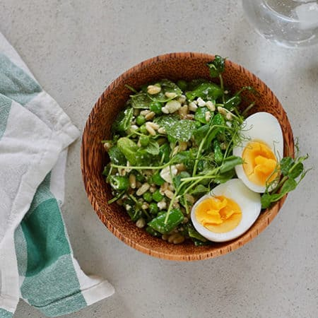 A bowl of pea salad topped with a hard boiled egg with a green and white napkin to the side