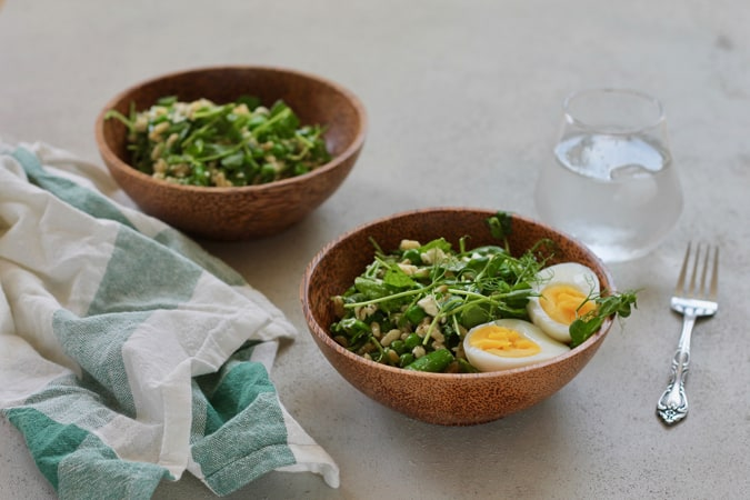 Two wooden bowls of pea salad with a glass of ice water, a green and white tea towel, and a silver fork in the background