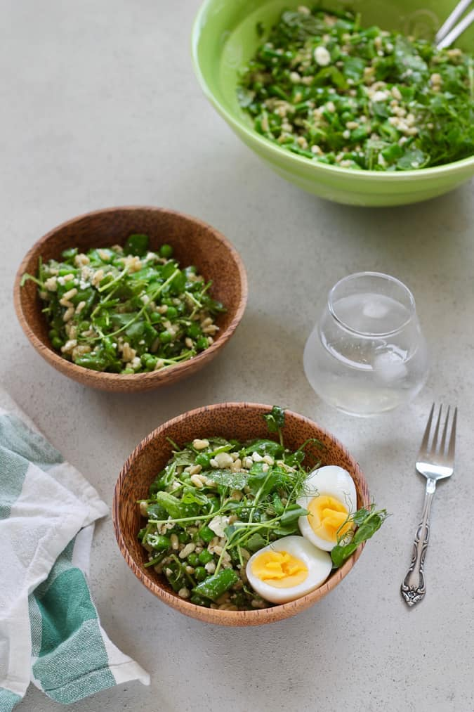Two wooden bowls with pea salad on a grey background, with a larger green bowl of pea salad in the background