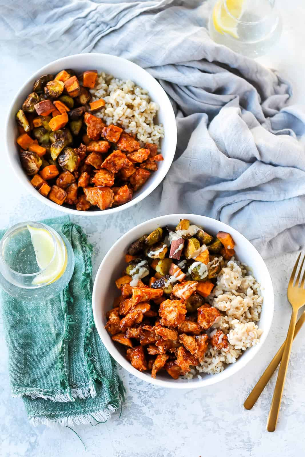 overhead photo with two white bowls with bbq tofu and roasted vegetables