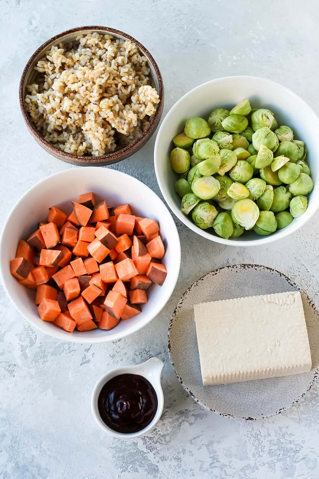 overhead photo with brown rice, tofu, sweet potato, brussels sprouts, and barbecue sauce