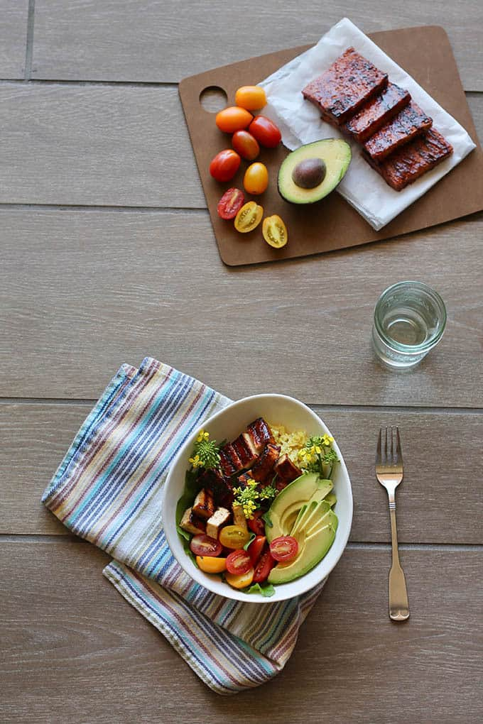 a white bowl with barbecue tofu, avocado, and red and yellow cherry tomatoes on a grey background with a glass of water, a striped napkin, and a fork to the side