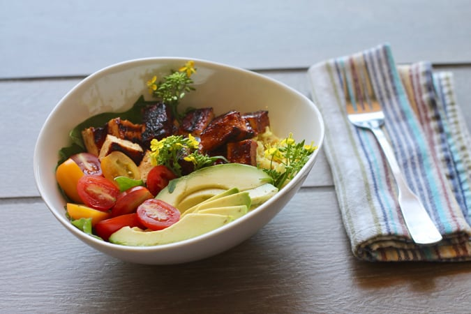 A white bowl with barbecue tofu, avocado, and cherry tomatoes over rice on a grey tile background with a striped napkin and a fork to the side