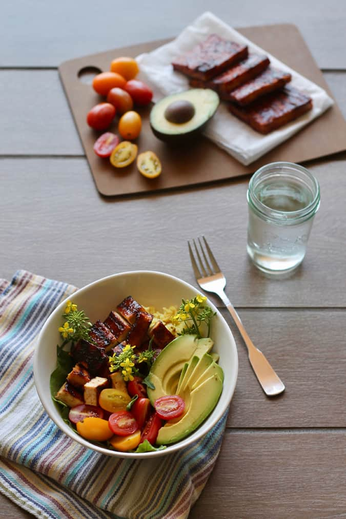 A white bowl with barbecue tofu, avocado, tomatoes, and edible flowers on a grey tile background with tray of ingredients and a glass of water in the background