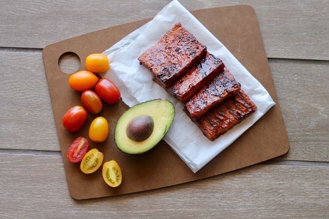 slices of barbecued tofu, half an avocado, and some red and yellow cherry tomatoes on a wooden cutting board