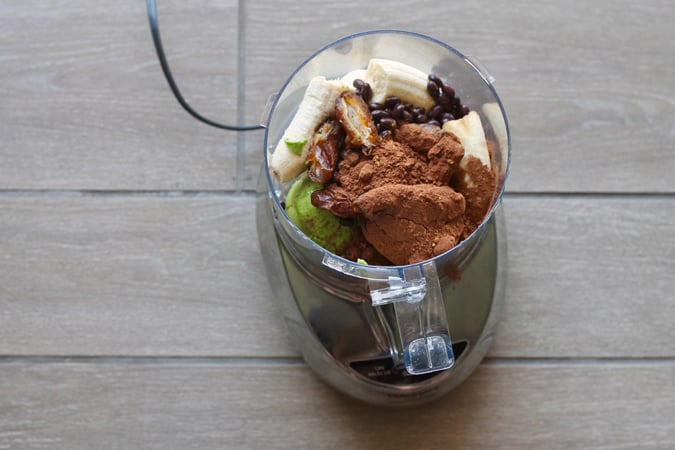 Banana, avocado, cocoa powder, beans, and dates in a food processor