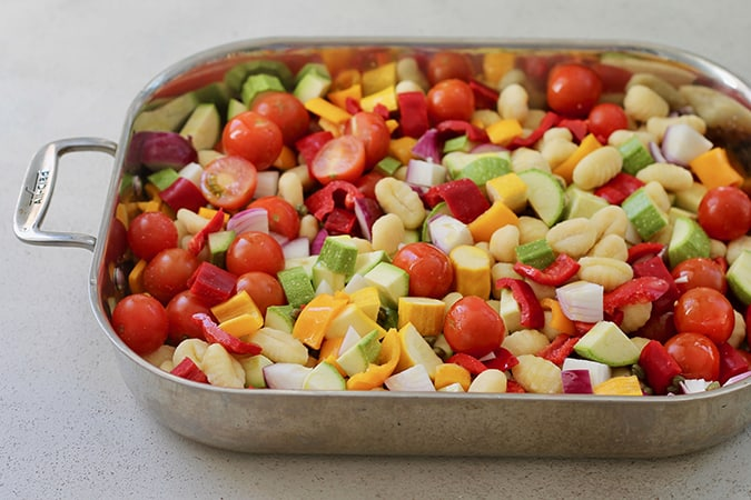 A sheet pan with vegetables and gnocchi on a grey background