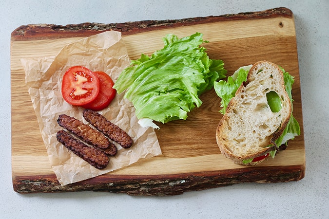 A wooden cutting board with a tempeh bacon BLT sandwich on it plus extra sandwich fixings to the side