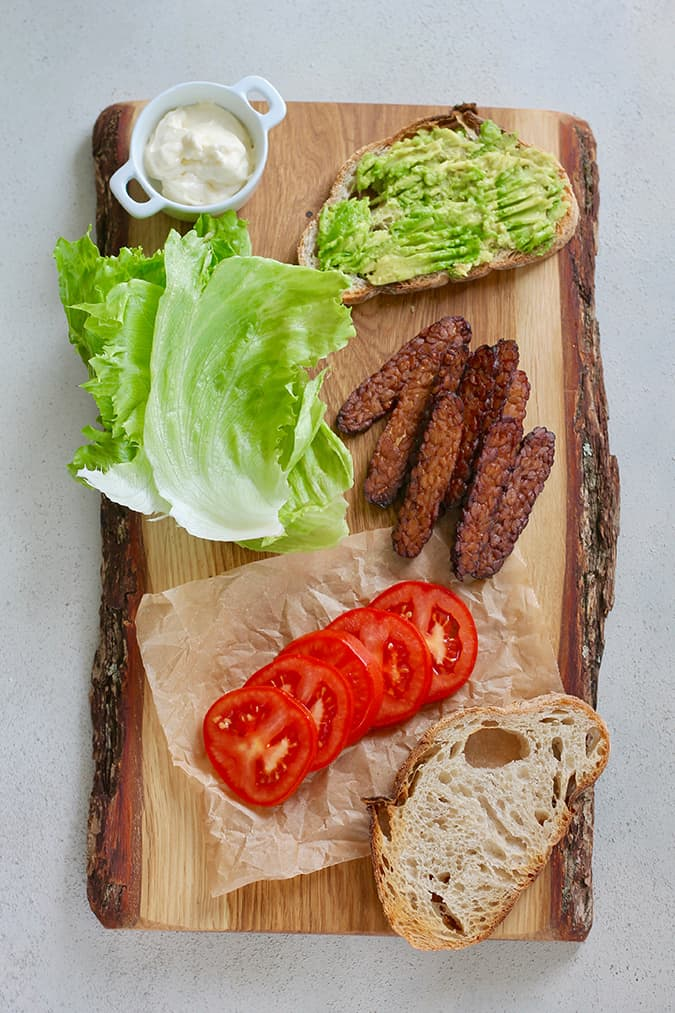 a wooden cutting board with tempeh bacon, bread spread with avocado, lettuce, and sliced tomatoes arranged on it