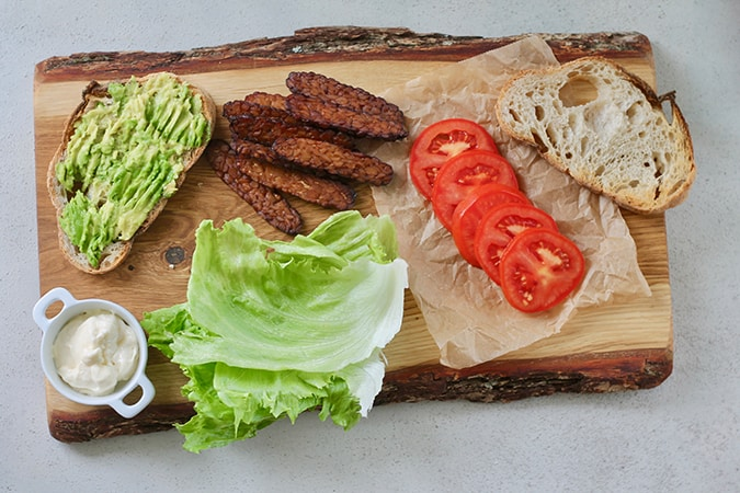 A wooden cutting board with all the fixings for a tempeh bacon BLT sandwich on it