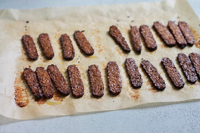 Strips of baked tempeh bacon on a sheet of parchment paper
