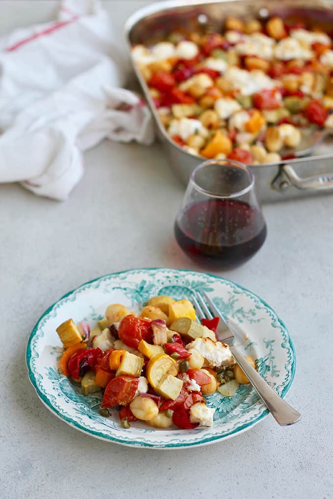 A plate of vegetarian baked gnocchi with a glass of wine and a sheet pan in the background
