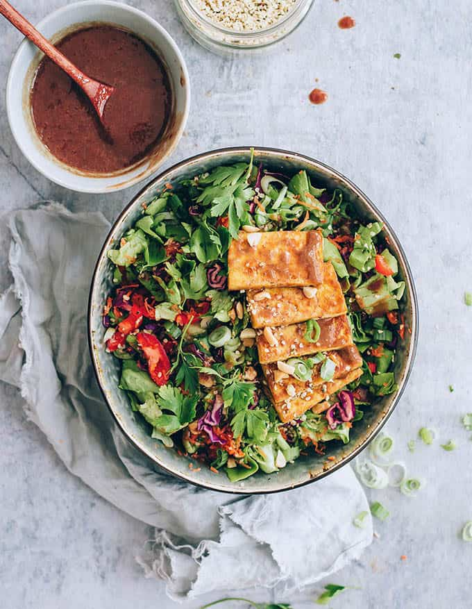 vegetarian lunch ideas: salad bowl topped with baked tofu on a grey background