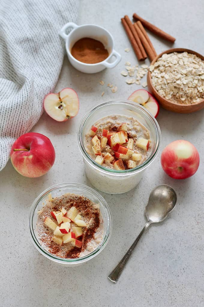 apple overnight oats in glass jars on a grey background