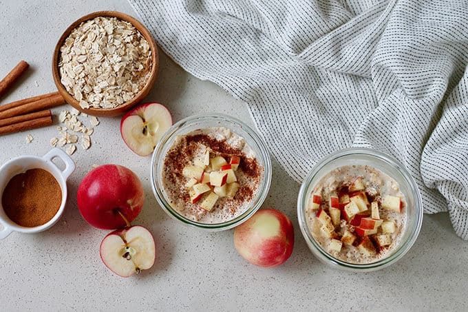 apple overnight oats on a grey background with apples and cinnamon sticks
