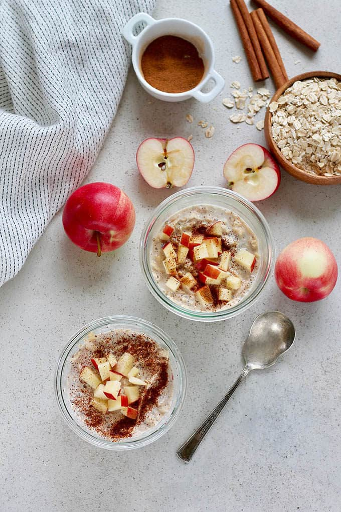 two glass jars of apple overnight oats with apples, oats, and cinnamon on a grey background