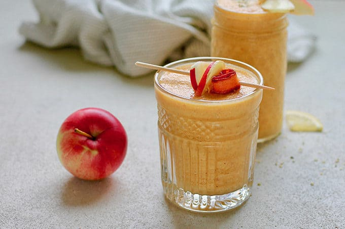 carrot apple ginger smoothie with a red apple on a grey background