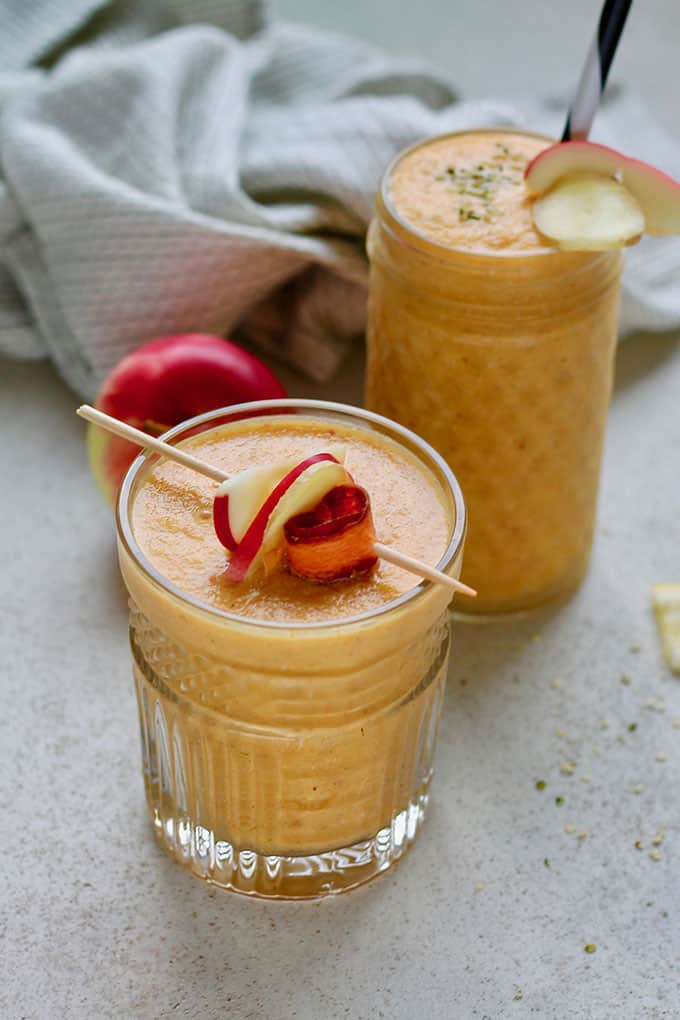 two glasses of carrot apple smoothie on a grey background garnished with apple slices