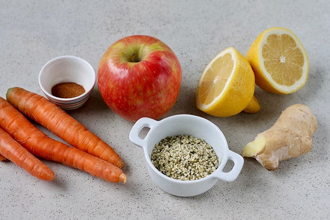 carrots, cinnamon, apples, ginger, hemp seeds, and lemons on a grey background