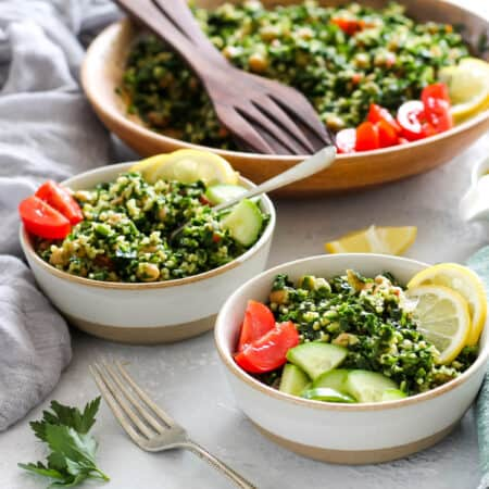 two bowls of kale tabbouleh salad on a grey background