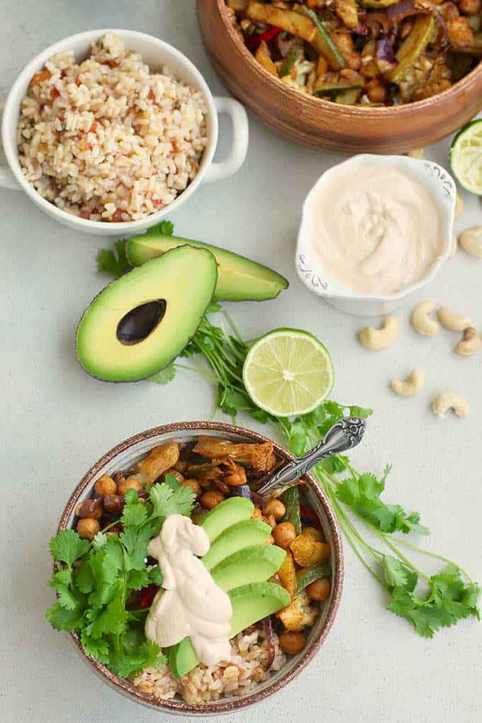 a fajita bowl made with chickpeas and vegetables on a grey background with rice, cashews, avocado, and lime