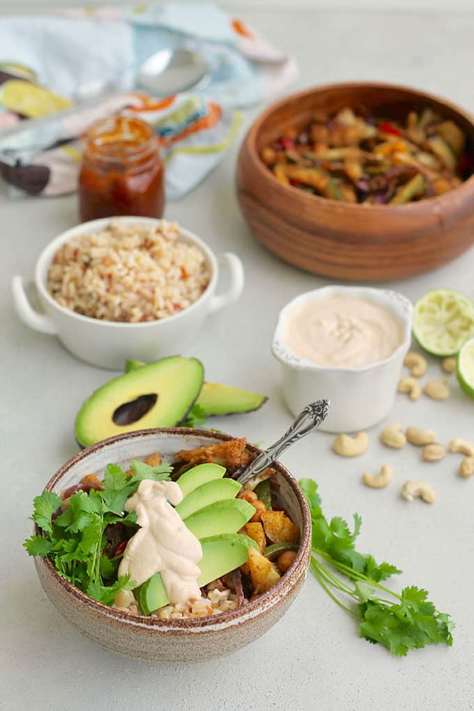 vegan fajita bowl topped with avocado and cilantro on a grey background with extra ingredients in the background