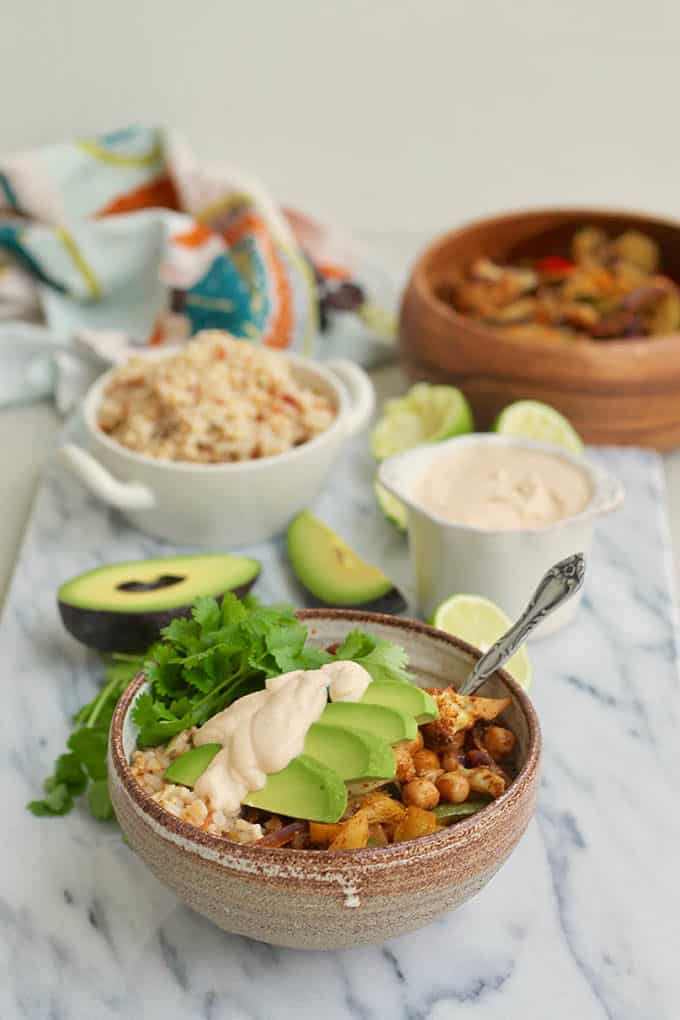 vegan fajita bowl in a ceramic bowl with rice and vegetables in the background