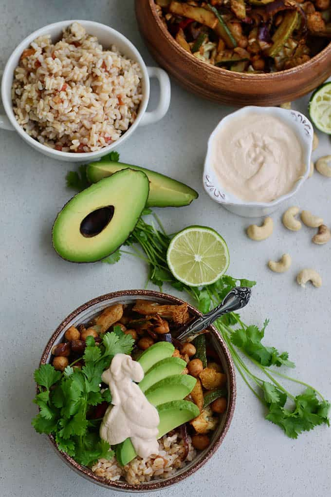 A fajita bowl topped with avocado and cashew cream with lime, cashews, and rice in the background