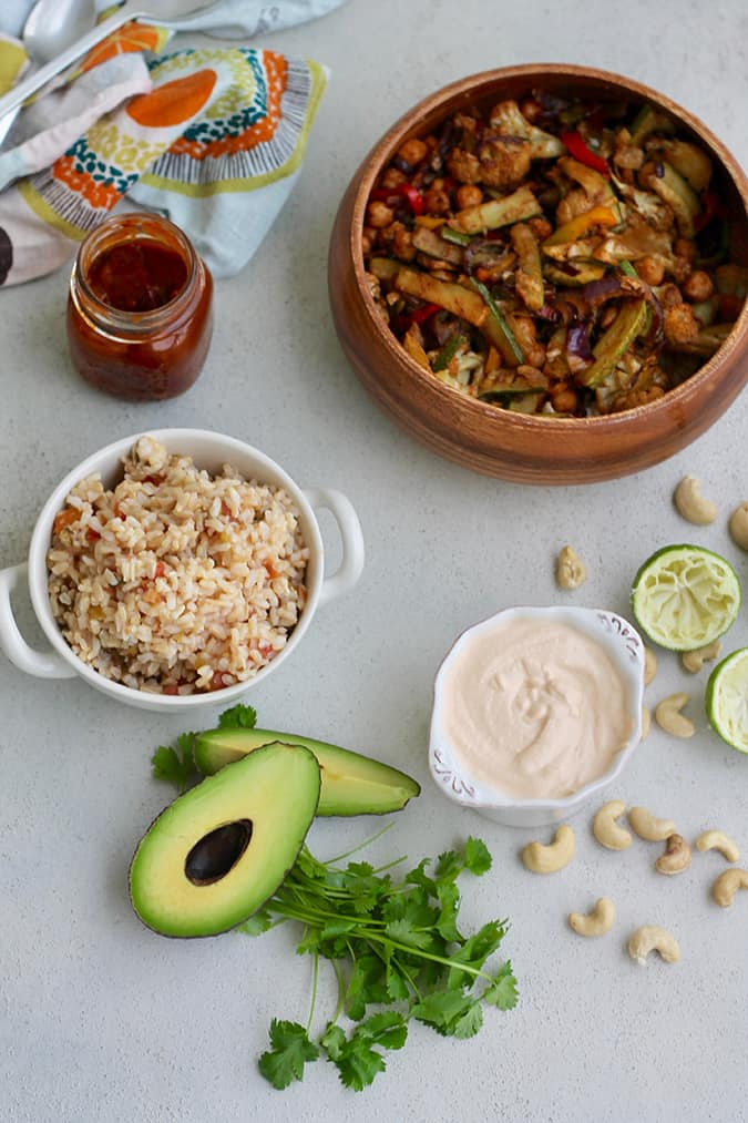 A wooden bowl of fajita filling, a small bowl of brown rice, a jar of sauce, some scattered chickpeas and avocado