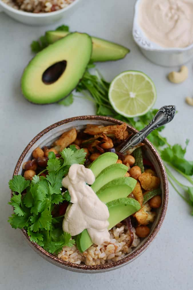 An overhead photo of a fajita bowl with rice, avocado, cilantro, and chickpeas