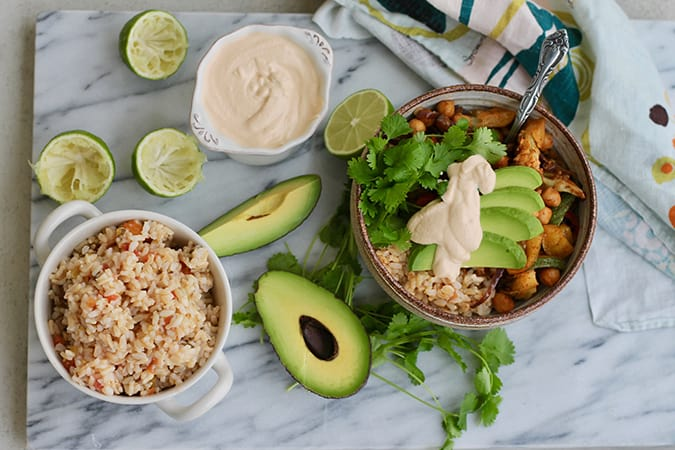 A marble cutting board with a bowl of rice, an avocado, juiced limes, and a fajita bowl