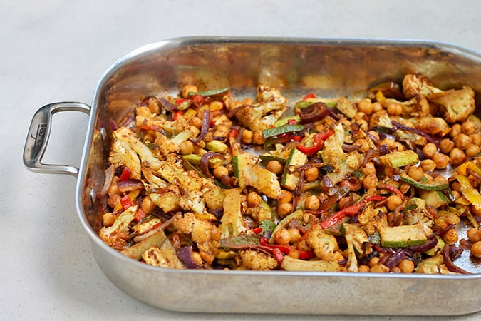 A roasting pan with cauliflower, zucchini, peppers, and chickpeas