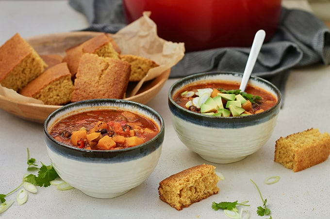 Two bowls of vegetarian black bean chili with corn bread on a grey background