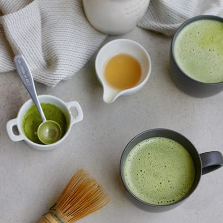 overhead shot of two matcha lattes, a whisk, matcha powder, and a tea towel on a grey background