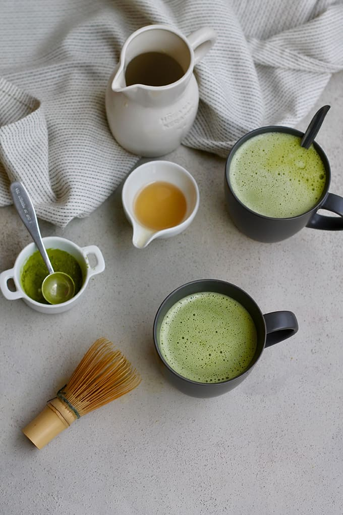 overhead photo of two matcha lattes in grey mugs