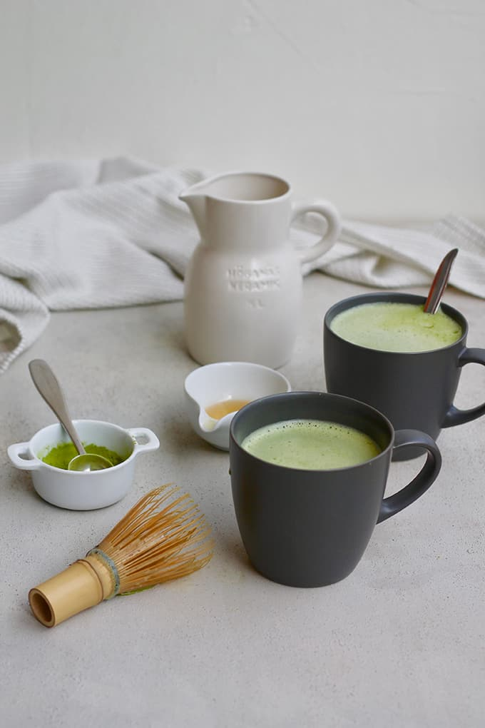 two black mugs with matcha latte on a grey background with a matcha whisk, matcha powder, honey, and a milk jug