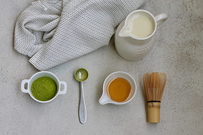 matcha powder, a measuring spoon, a jar of honey, a whisk, and a jug of milk on a grey background