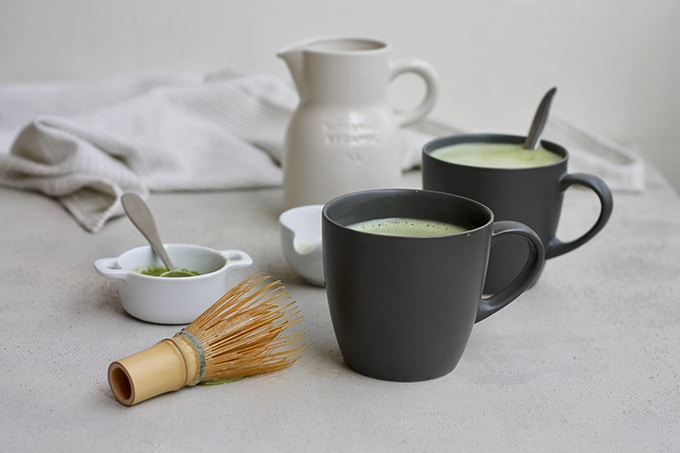 two black mugs with matcha, a jug of milk, and a whisk on a grey background