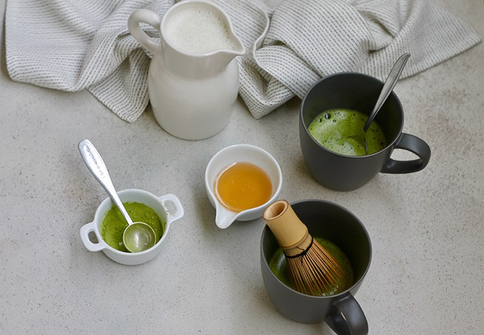 Two black mugs with matcha powder in them and a whisk in one mug