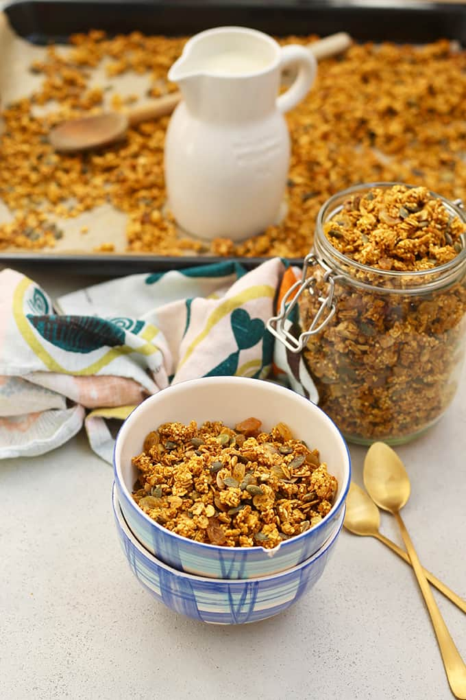 A bowl of pumpkin granola on a grey background with two golden spoons, a tea towel, a jar of pumpkin granola, and a jug of milk in the background