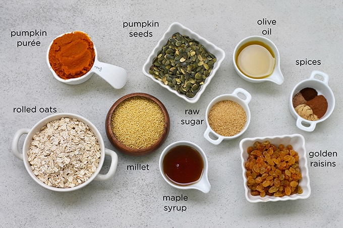pumpkin puree, rolled oats, millet, pumpkin seeds, olive oil, raw sugar, maple syrup, golden raisins, and spices on a grey background
