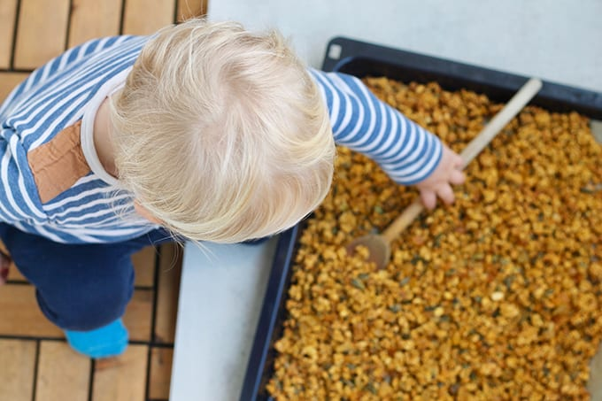 A blond toddler stirring a pan of granola